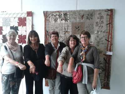 From Left to right, Jeannien, Marie Ange, Kathy, Me, and Catherine, in front of a beautiful quilt, flashing our orange arm bands.