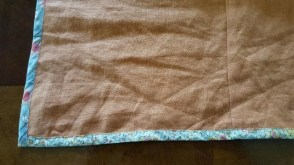 Right side of the orange linen with bound hem.