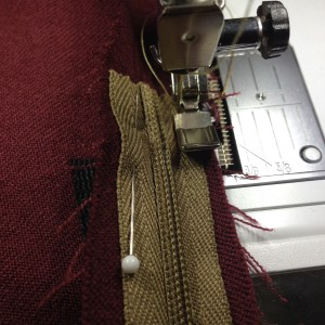 Sewing end of zipper tape to seam allowance.
