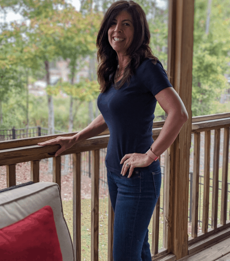 Stephanie standing on porch blue shirt and jeans