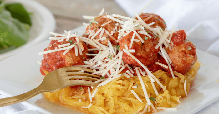 baked meatballs with spaghetti squash on a white plate with a fork