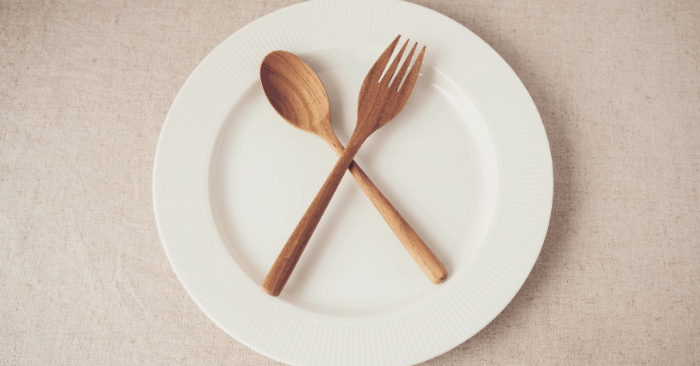 empty plate with fork and spoon laying on top during intermittent fasting
