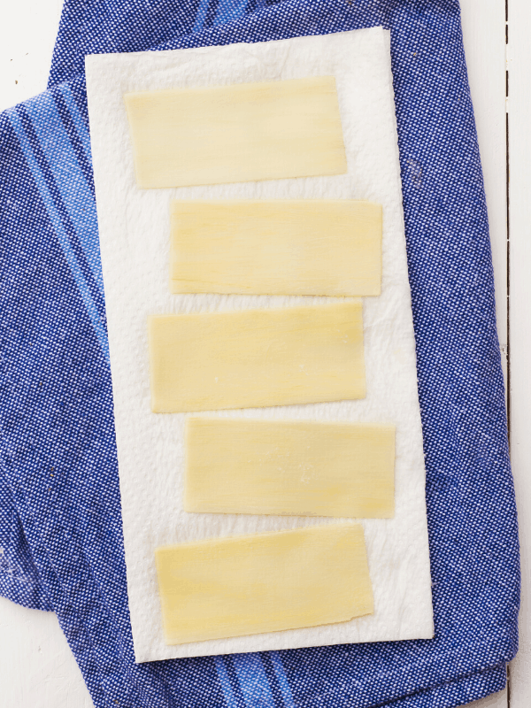 sheets of palmini pasta laying on paper towels to dry after soaking milk