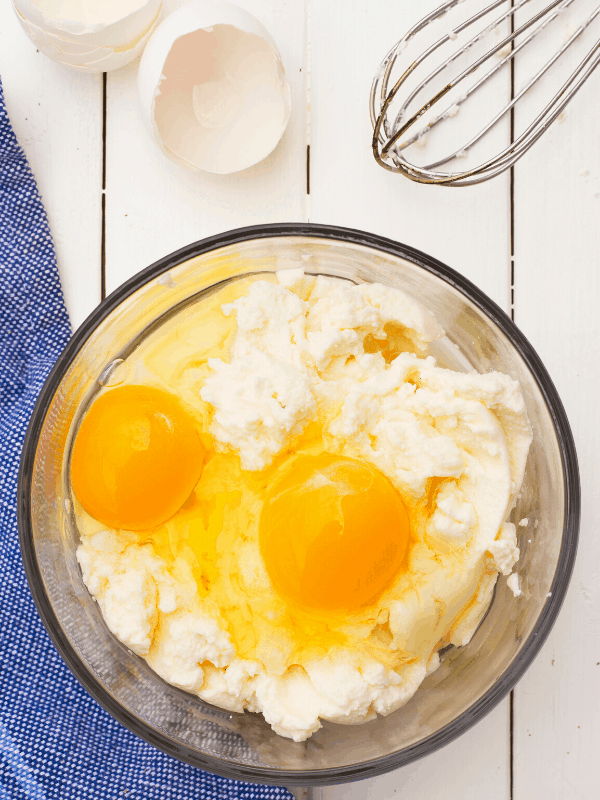 ricotta cheese with 2 eggs ready to be mixed in a bowl