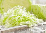 cabbage on a cutting board with shredded cabbage