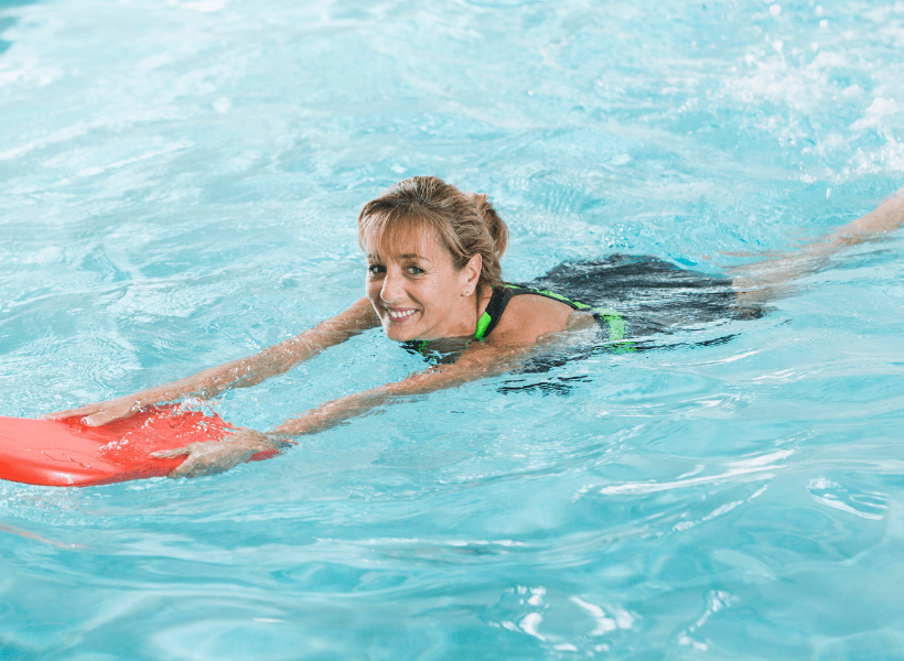 woman using kickboard for pool workout