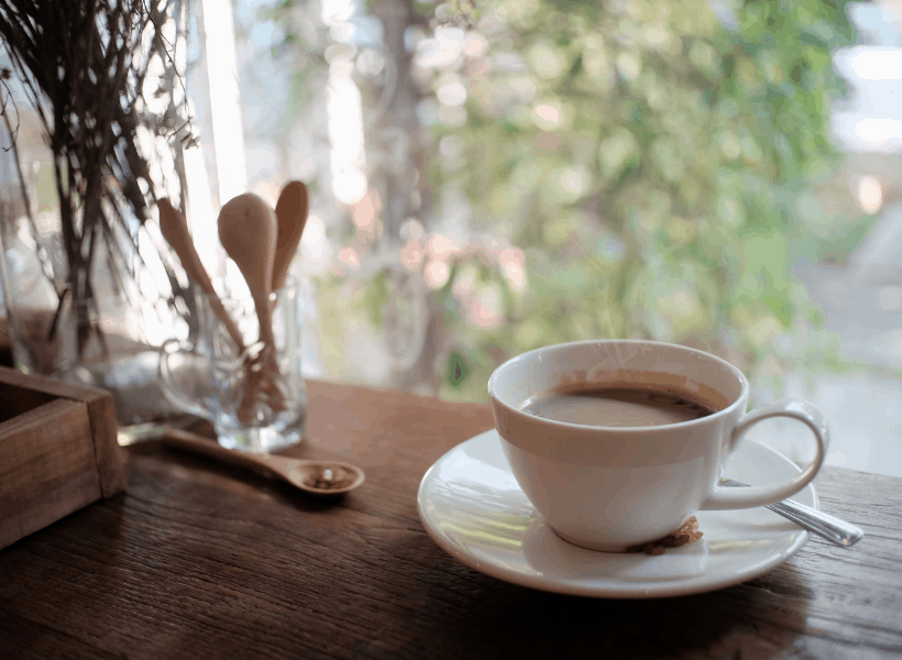 cup of coffee on table by a window