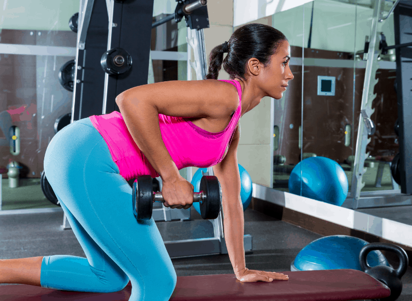 woman in gym doing one arm bent over rows