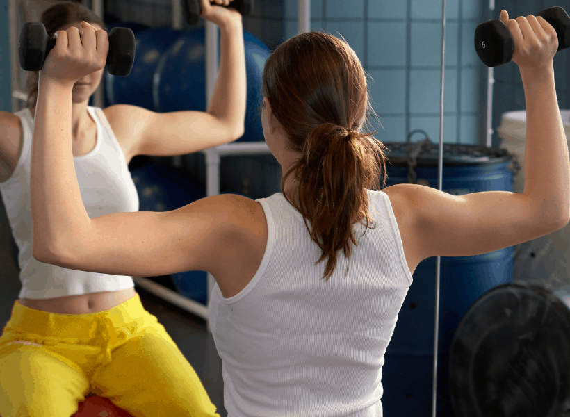 woman using weights for arm beginner's strength training