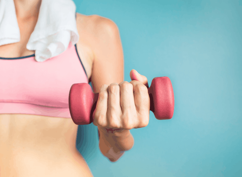 woman with sports bra on, towel around neck holding a dumbbell in hand while weight lifting