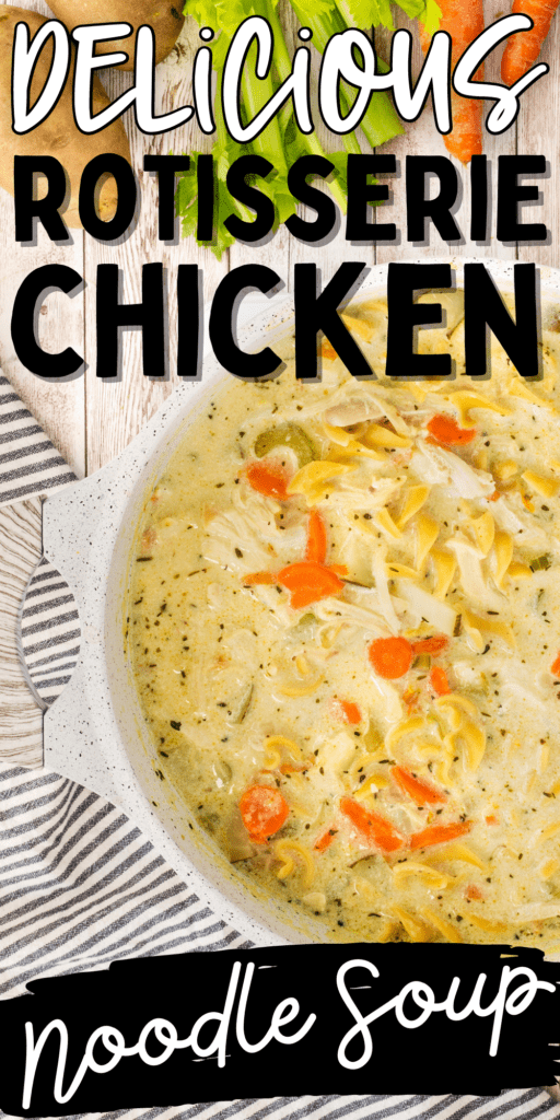 large white dutch oven full of creamy chicken noodle soup with carrots, egg noodles, celery and chicken on a table with fresh vegetables beside pot
