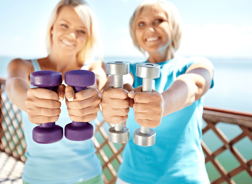 2 women holding hand weights silver medal and purple neoprene dumbbells out to show us