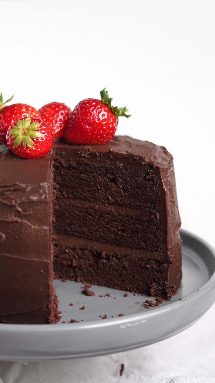 vegan layered chocolate cake with strawberries. The best cake you will ever try. It's super rich, moist and perfect for chocoholics.