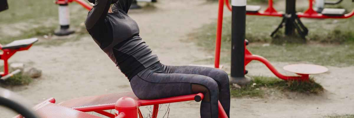 faceless woman in protective mask working out at street simulator