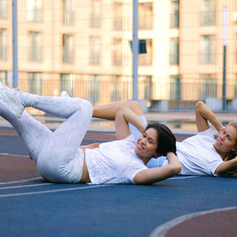 ladies doing abs exercise on sports ground