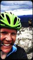 This image shows me in close up, wearing a bright green helmet and holding my glasses in my teeth, at the Caesar's Head mountain lookout.