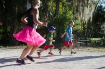 lady in costume running with kids