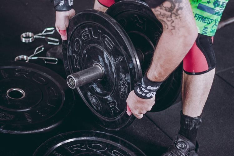 A man is unloading a barbell. He's not stronger than he was a month ago and he has to remove the extra weight he added