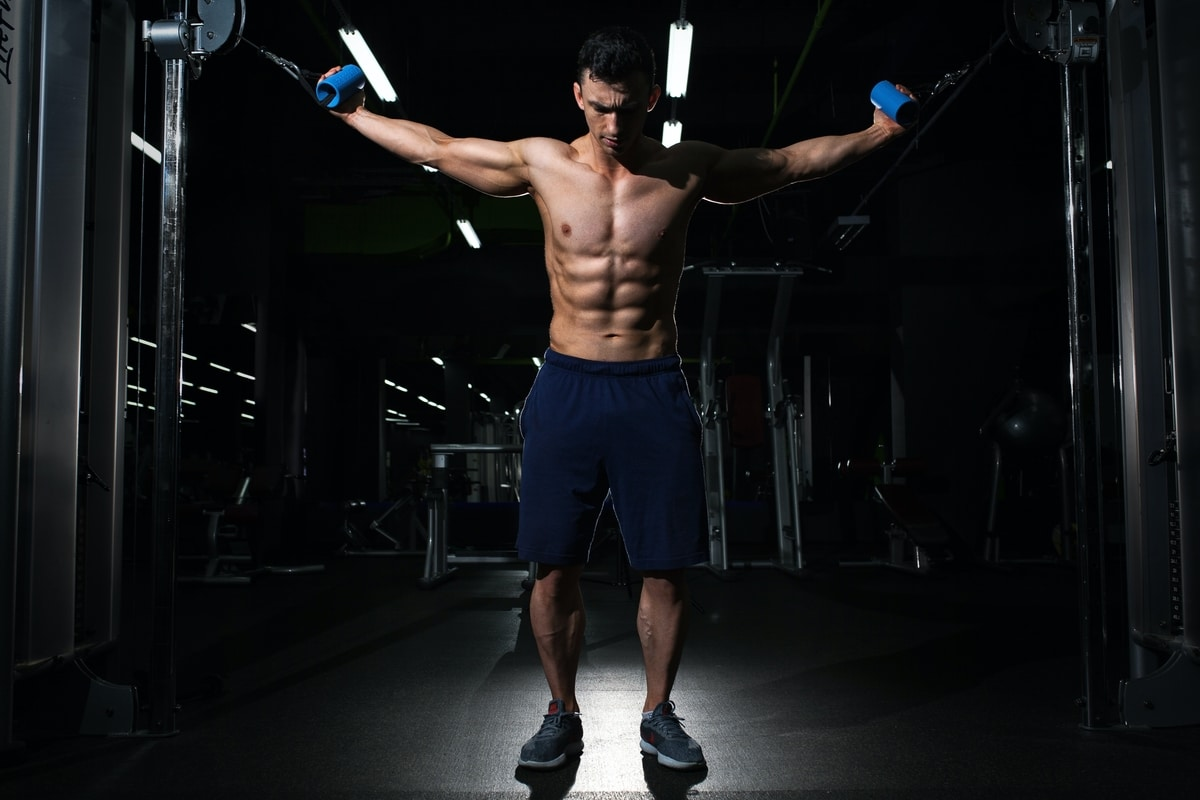 A man with abs are standing, holding a cable in each hand.