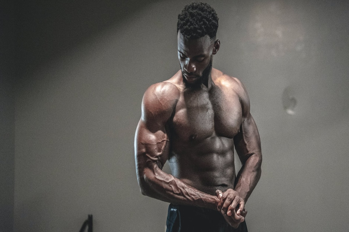 A very muscular man is flexing. To get a physique like his, hard workouts won't be enough. You'll have to eat right and hit your macros.