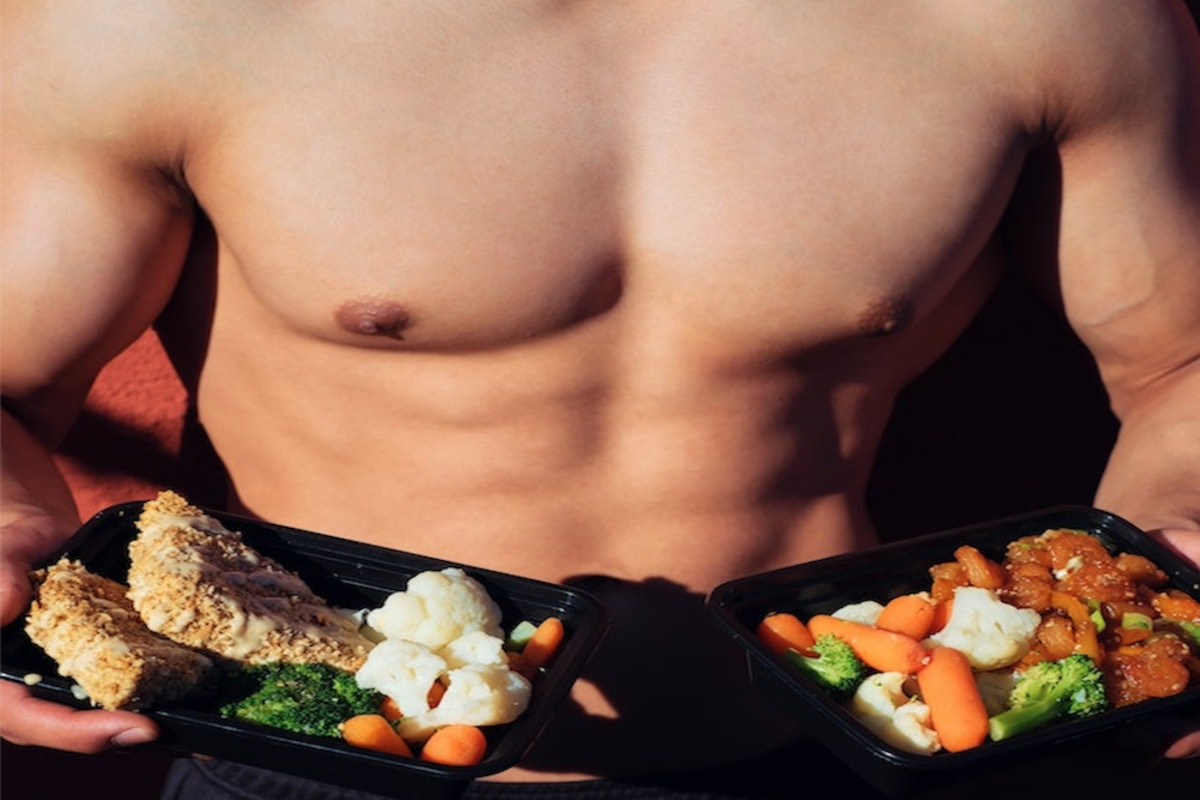 A fit man without a shirt is holding a healthy meal in his hands. He shredded down without cardio by focusing on lifting heavy and eating in a deficit.