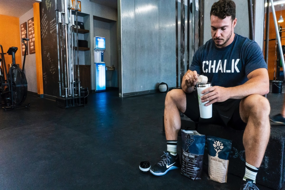 A man is sitting on a bench, drinking his protein shake after a hard workout. He knows why protein are important