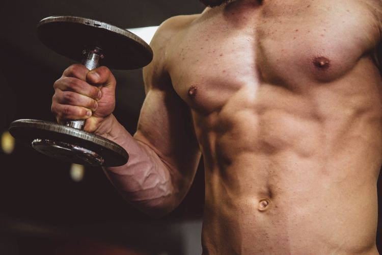 A man is curling with a dumbbell. He's on a dumbbels workout for arms workout plan.