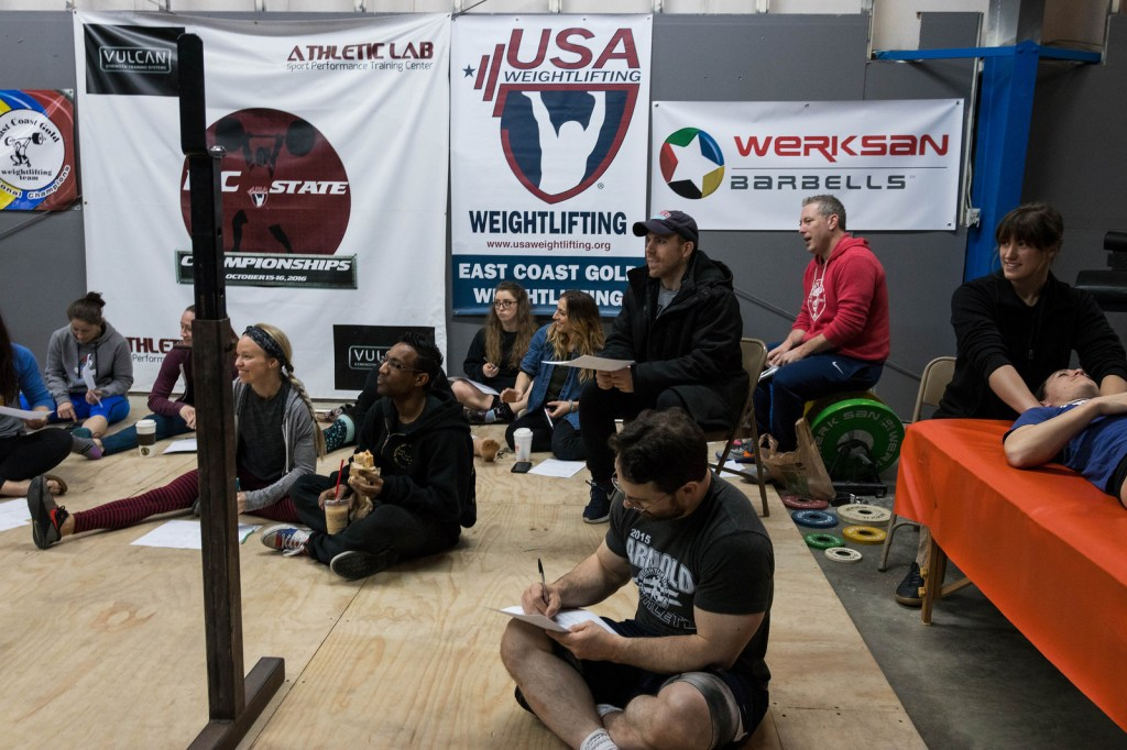 Group of people listening to Coach Leo Totten speak on positive reinforcement in wieghtlifting
