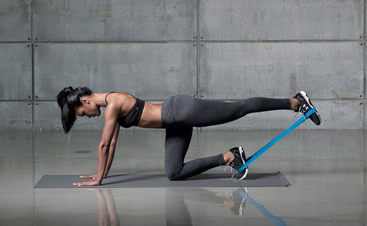 Woman Working Out Glute Kickback Using Resistance Band