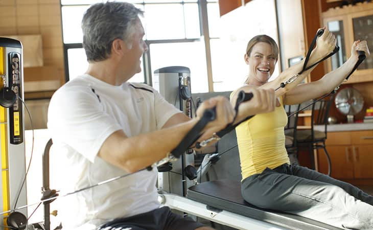 Couple Using Total Gym For Workout