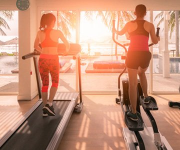 Women Using Treadmill and Elliptical Machine For Fitness