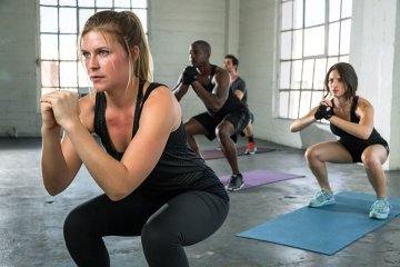 Group of Fitness People Doing Squat Pulses