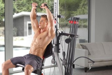 Man Using Bowflex Revolution Home Gym