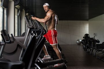 Man Working Out In Elliptical Bike For Fitness