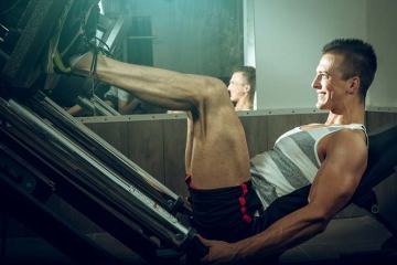 Man Using Leg Press Machine For Fitness