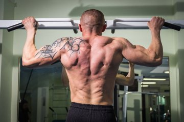 Man Using Pull Up Bars For Fitness