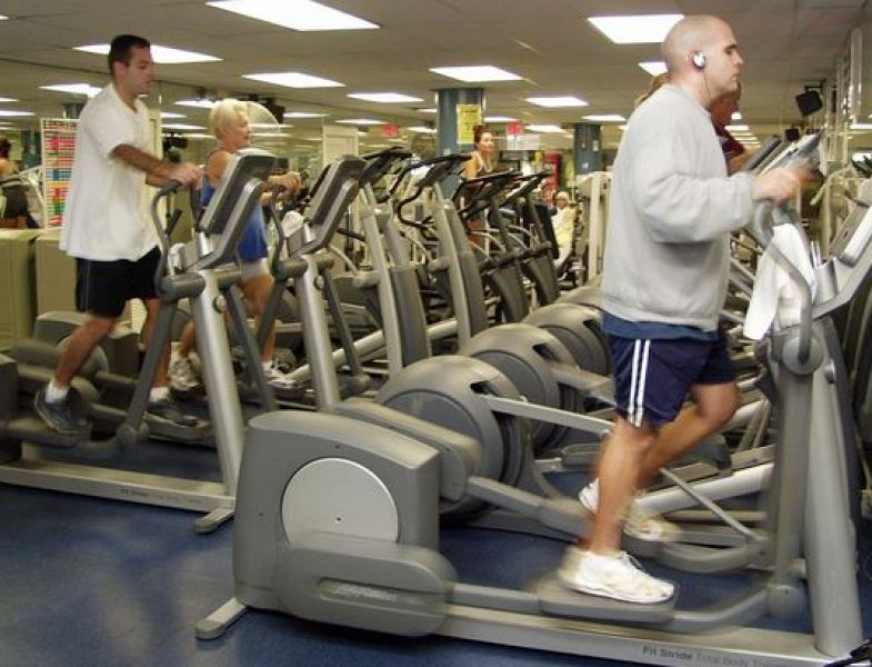 People using elliptical machines at gym