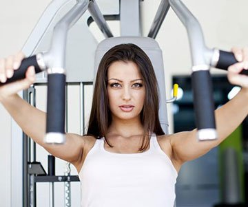 Woman Using Shoulder Press Machine