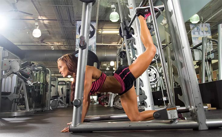Woman Working Out Glute Kickback Using Smith Machine