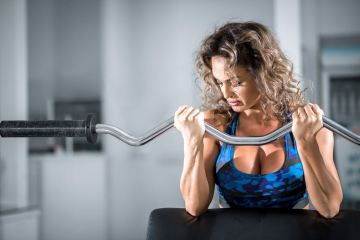 Woman doing curls on preacher curl bench
