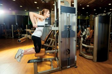 Fit Woman Using Dip Machine Gym