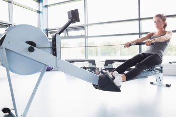 Woman Using Rowing Machine For Fitness