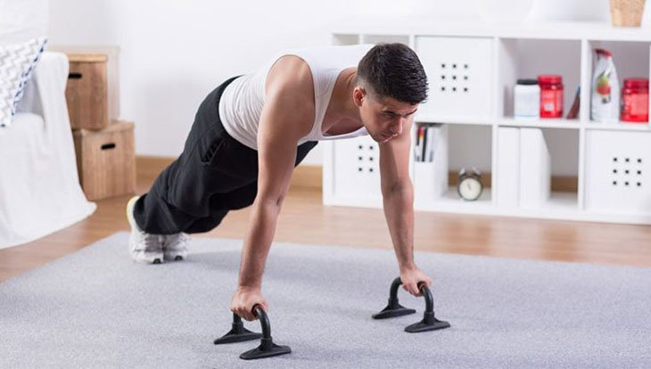 Man Working Out Using A Push Up Bar