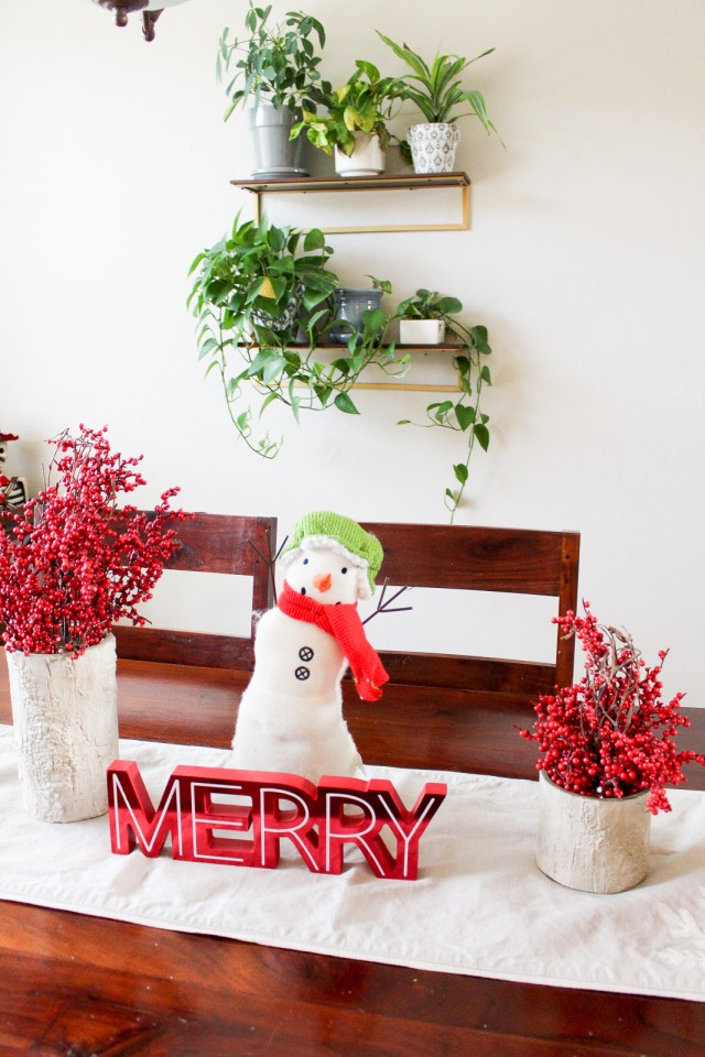 Holiday decoration of snowman on dining room table with two cranberry centerpieces and a sign that says Merry