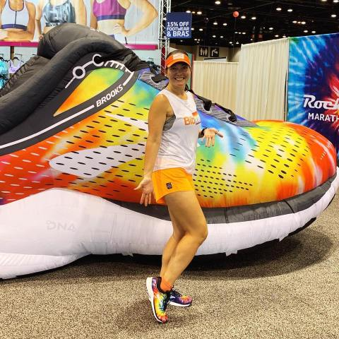 Standing in front of an inflatable Brooks Launch shoe while wearing my new, matching rainbow tie-dyed shoes.