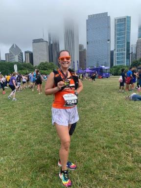 Standing at the Rock N Roll Chicago finishers festival showing my half marathon medal with the Chicago city skyline in the background.