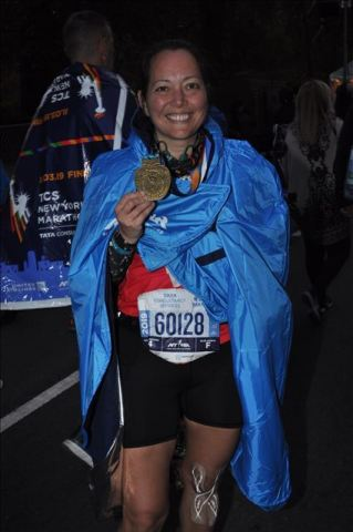 Wearing my blue NY marathon poncho and showing off my medal.
