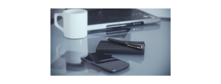 coffee cup, laptop, phone, notebook and pen neatly on a desk