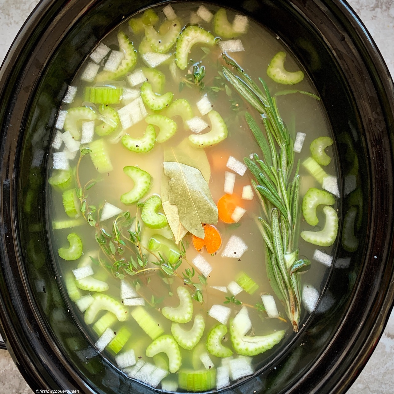 pic of raw chicken, broth, celery, onion, and carrots in the slow cooker for Slow Cooker Instant Pot Chicken Soup (Low-Carb, Paleo, Whole30) (1)