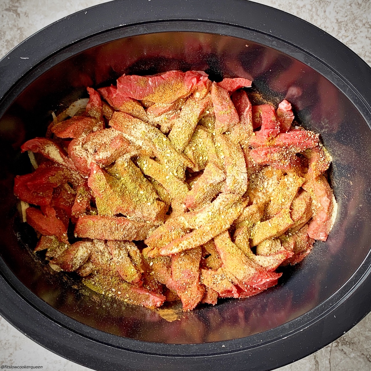 beef shawarma in the slow cooker covered with spices before being stirred